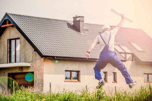 Man jumping for joy outside home that he has implemented condensation solutions