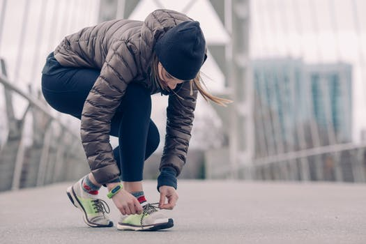 Woman in hat and jacket tying her shoelace before she is exercising outside