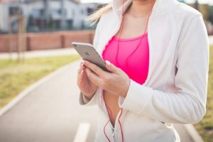 Woman with iPhone and headphones in picking a song before exercising